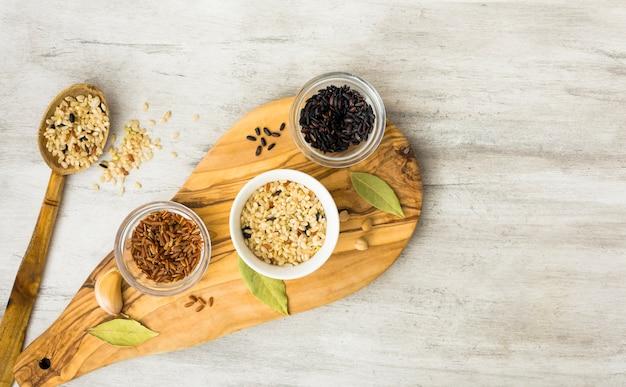Différents types de riz dans des bols sur une planche en bois avec une cuillère Photo gratuit