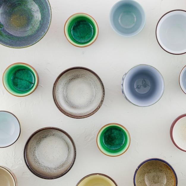Différents types de tasses à thé en céramique isolés sur fond texturé blanc Photo gratuit