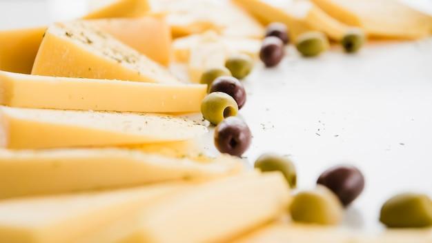 Différents types de tranches de fromage avec des olives sur fond blanc Photo gratuit
