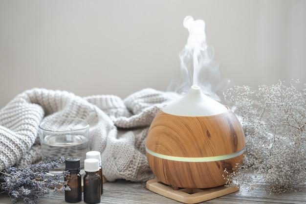 Diffuseur D'huile D'arôme Moderne Sur Surface En Bois Avec élément Tricoté, Eau Et Huiles Dans Des Pots. Photo Premium