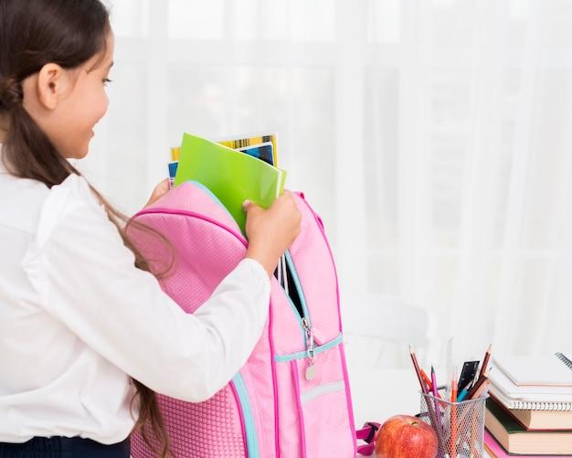 Diligent écolière emballant cartable au bureau Photo gratuit