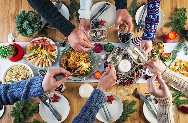 Dinde Au Four. Dîner De Noël. La Table De Noël Est Servie Avec Une Dinde, Décorée De Guirlandes Lumineuses Et De Bougies. Poulet Frit, Table. Dîner De Famille. Vue De Dessus, Mains Dans Le Cadre Photo gratuit