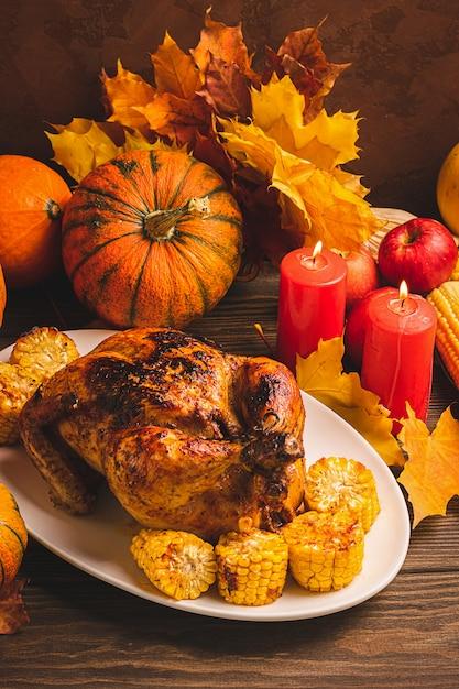 Dinde festive ou poulet cuit au four par thanksgiving sur plaque blanche et une récolte de légumes de saison: pommes de maïs à la citrouille Photo Premium
