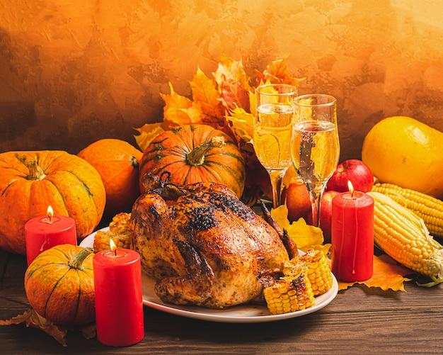 Dinde de fête ou poulet cuit au four par thanksgiving deux verres de récolte de vin de légumes de saison sur une table rustique. Photo Premium