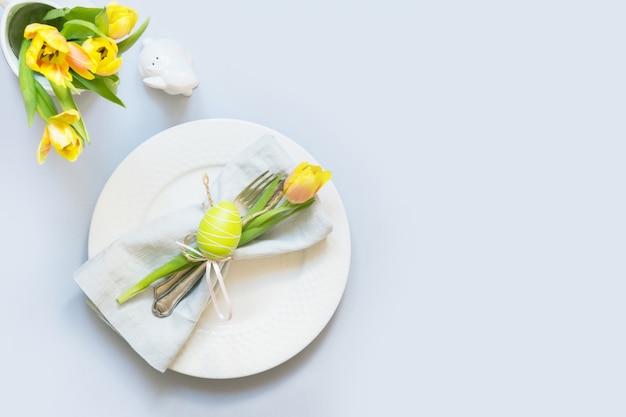 Dîner de pâques réglage de la table avec une tulipe jaune sur la table. vue de dessus. Photo Premium