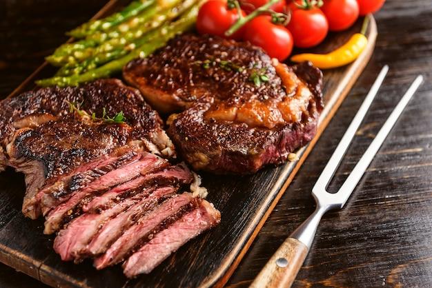 Dîner Pour Deux Délicieux Steaks Juteux, Asperges Au Parmesan Et Légumes. Photo Premium