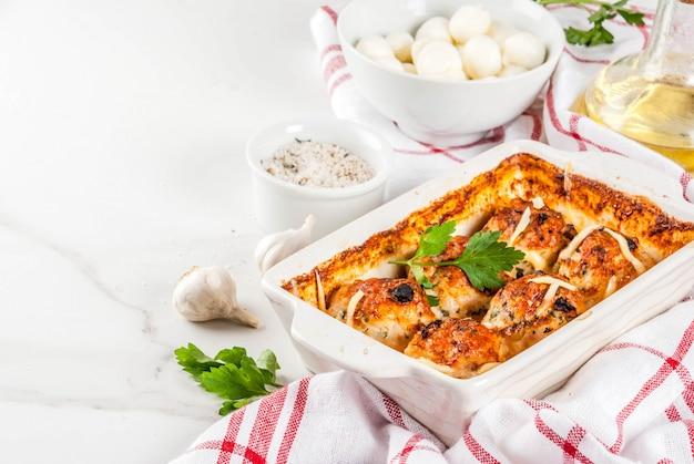 Dîner de régime sain fait maison, boulettes de dinde au poulet préparées avec sauce, fromage, légumes verts. sur une table en marbre blanc, avec des épices. Photo Premium