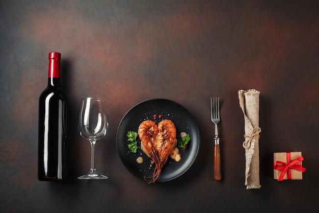 Dîner romantique avec des crevettes en forme de coeur et du vin sur un fond marron. vue de dessus avec espace de copie Photo Premium