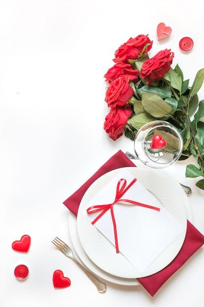 Dîner de la saint valentin. réglage de la table romantique avec des roses rouges. vue d'en-haut. Photo Premium