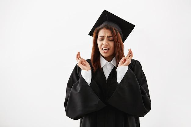 Diplômée Africaine En Manteau Noir Priant Sur Une Surface Blanche Photo gratuit