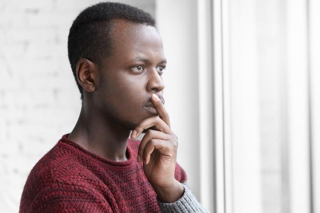 Directeur Artistique Afro-américain Inquiet Pensif Habillé Avec Désinvolture Gardant Le Doigt Sur Les Lèvres Photo gratuit