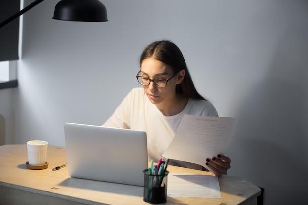 Directeur du millénaire dans des verres travaillant sur un ordinateur portable et tenant le document Photo gratuit