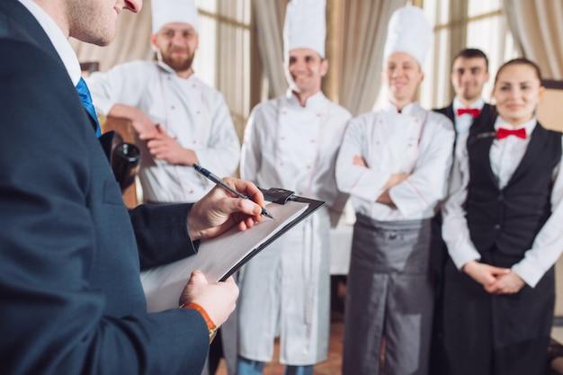 Directeur du restaurant et son personnel en cuisine. interagissant avec le chef cuisinier dans la cuisine commerciale. Photo Premium