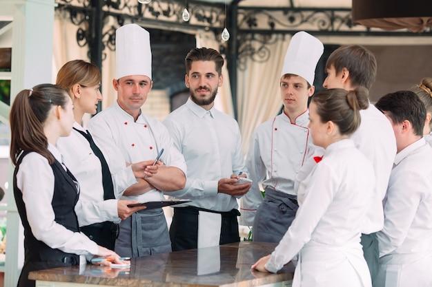 Directeur du restaurant et son personnel en terrasse. interagir avec le chef cuisinier au restaurant. Photo Premium