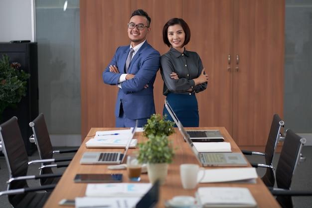 Dirigeants Asiatiques Masculins Et Féminins Posant Au Sommet De La Table De Réunion Dans La Salle De Conseil Photo gratuit