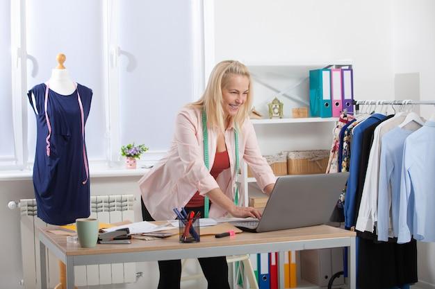 Discussion Du Projet De Création De Vêtements Avec Le Client Par Téléphone, Skype. Femme, Conversation Téléphone, Quoique, Debout, Table, Dans, L'atelier Photo Premium
