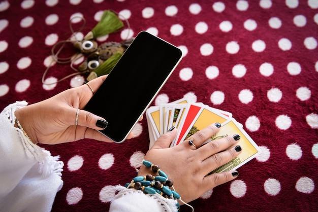 Diseuse De Bonne Aventure Lire Des Lignes De La Fortune Sur L'application Smartphone De L'horizon En Ligne Horoscopes Modernes De Smartphone. Photo Premium