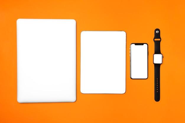 Dispositifs plats poser sur fond orange Photo gratuit