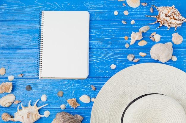 Disposition de coquillages et chapeau près du bloc-notes Photo gratuit
