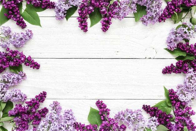 Disposition Créative Faite Avec Des Fleurs Lilas De Printemps Sur Fond En Bois Blanc. Mise à Plat. Vue De Dessus Photo Premium