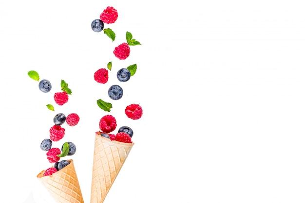 Disposition créative avec framboises et bleuets avec des cônes de crème glacée à la gaufre, motifs simples Photo Premium