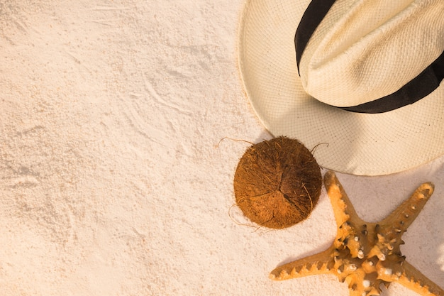 Disposition de l'été de chapeau de noix de coco et étoile de mer sur le sable Photo gratuit