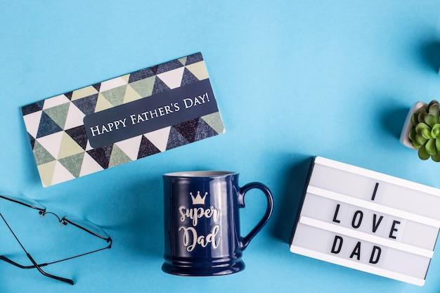 Disposition de la fête des pères avec un gobelet cadeau, une carte et l'inscription j'aime papa Photo Premium