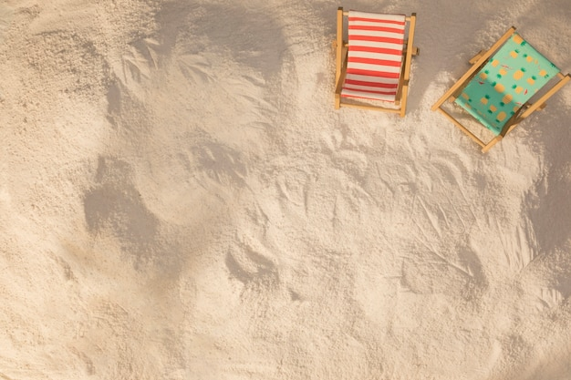 Disposition de petits transats décorés sur du sable Photo gratuit