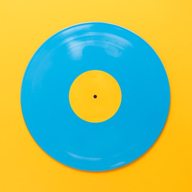 Disque de vinyle bleu plat lay avec fond jaune Photo gratuit