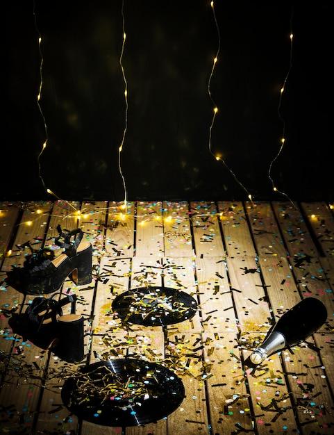 Disques vinyles, chaussures de femme et bouteille de boisson entre des confettis près du mur Photo gratuit