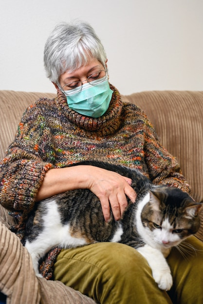Distanciation Sociale Du Coronavirus Due à Une épidémie Pandémique. Femme âgée Avec Un Masque Protecteur, Rester à La Maison Caressant Son Chat. Photo Premium