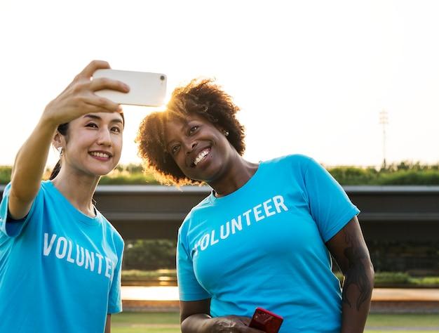Divers bénévoles prenant un selfie ensemble Photo gratuit
