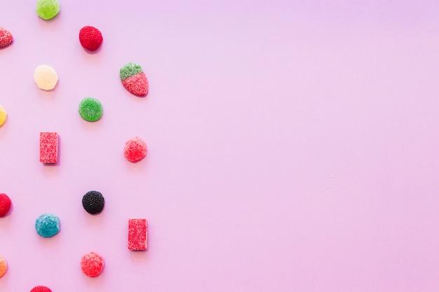 Divers bonbons colorés de gelée de sucre sur fond d'écran rose Photo gratuit