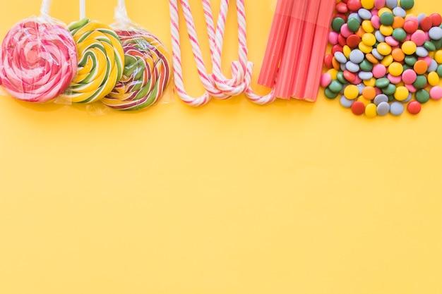 Divers bonbons colorés sur la toile de fond jaune Photo gratuit