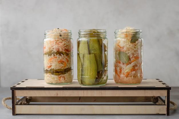 Divers Choux Fermentés Et Concombres En Pots Sur Une Surface Grise En Bois, Photo Premium