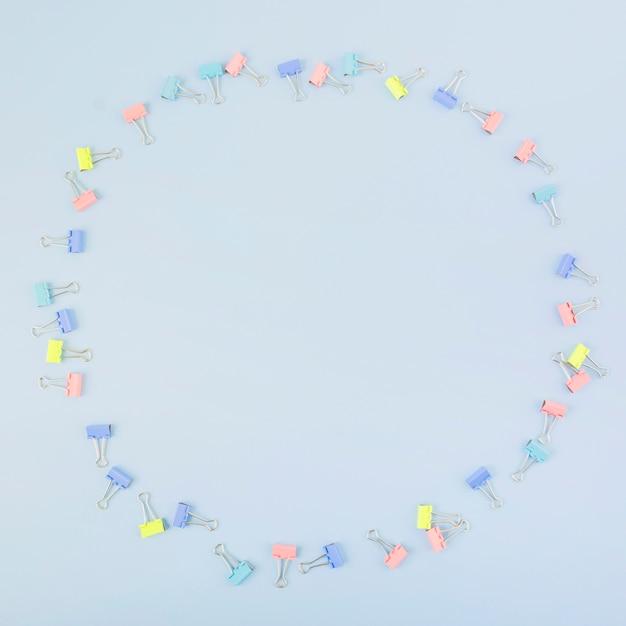 Divers clips de bulldog multicolores formant un cercle sur fond bleu Photo gratuit