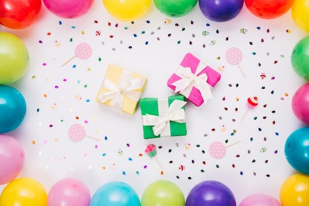 Divers coffrets cadeaux décorés de confettis; accessoires et ballons sur fond blanc Photo gratuit