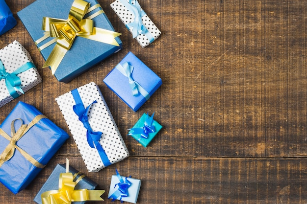 Divers coffrets cadeaux emballés et décorés de rubans sur une vieille table patinée Photo gratuit