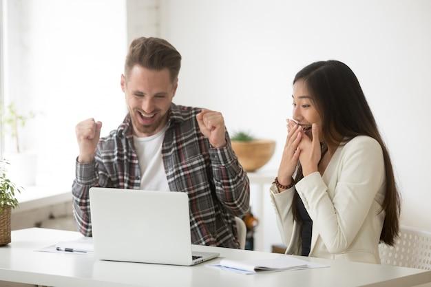 Divers collègues émerveillés par le succès en ligne ou les résultats obtenus Photo gratuit