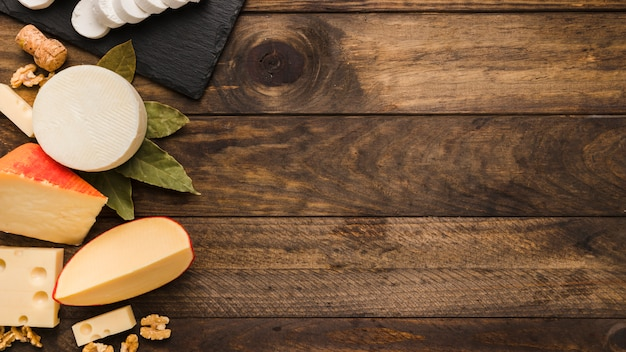 Divers délicieux fromage avec des feuilles de laurier et de noix sur bois texturé Photo gratuit