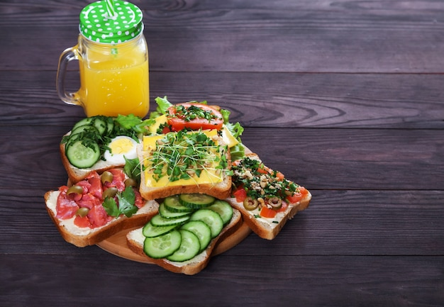 Divers Délicieux Sandwichs Au Saumon, Pousses, Tomates, Concombres, Herbes, Noix, Olives Et Jus D'orange Frais Photo Premium
