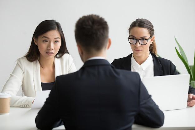 Divers directeurs de la gestion des ressources humaines, convaincus et non convaincus, interrogent un candidat masculin Photo gratuit