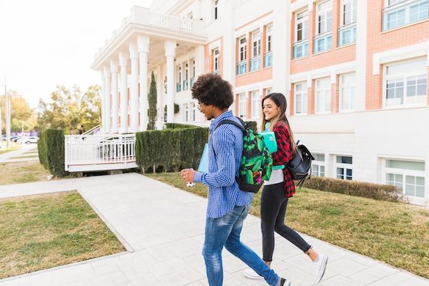 Divers étudiants de couple d'adolescents marchant ensemble à l'extérieur du bâtiment universitaire Photo gratuit