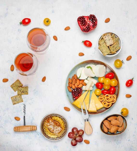 Divers Fromages Et Assiette De Fromages Sur Table Lumineuse Avec Différents Fruits à Coque Et Fruits Photo gratuit