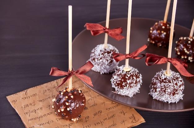 Divers gâteaux pop décorés avec du chocolat noir sur un fond marron Photo Premium