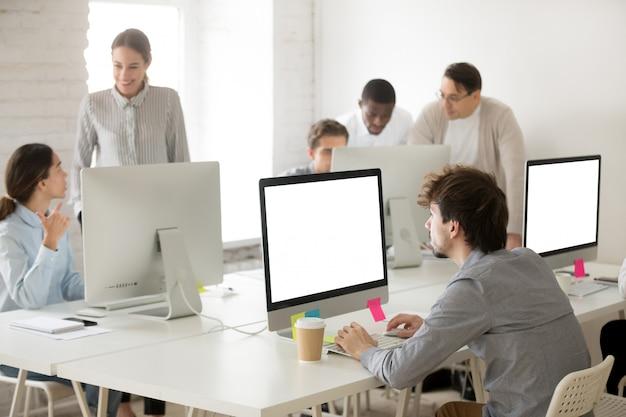 Divers groupes d'employés travaillant ensemble en utilisant des ordinateurs au bureau Photo gratuit