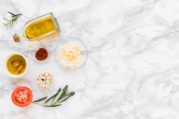 Divers ingrédients avec de l'huile sur fond de marbre blanc Photo gratuit
