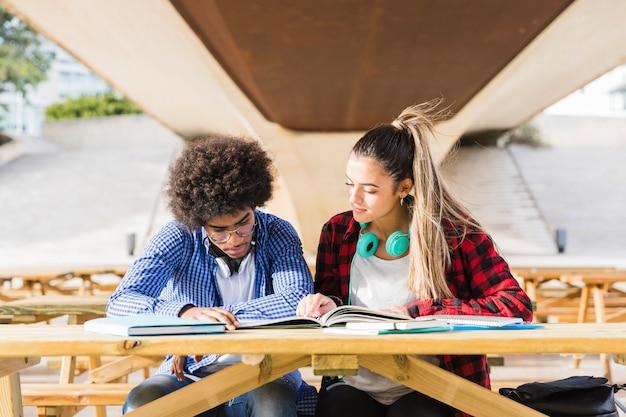 Divers jeune couple assis sur un banc en bois étudient ensemble sur le campus universitaire Photo gratuit