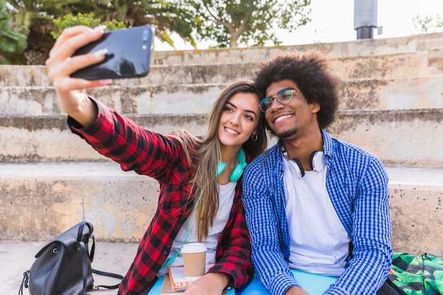 Divers Jeune Couple étudiant Assis Sur Un Escalier Prenant Selfie Sur Smartphone Photo gratuit
