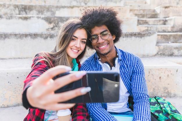 Divers jeune couple prenant selfie sur smartphone Photo gratuit